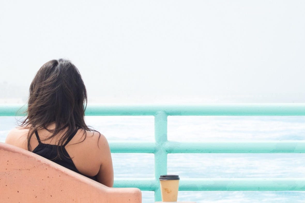 Girl facing away towards sea being present and thoughtful with cup of coffee