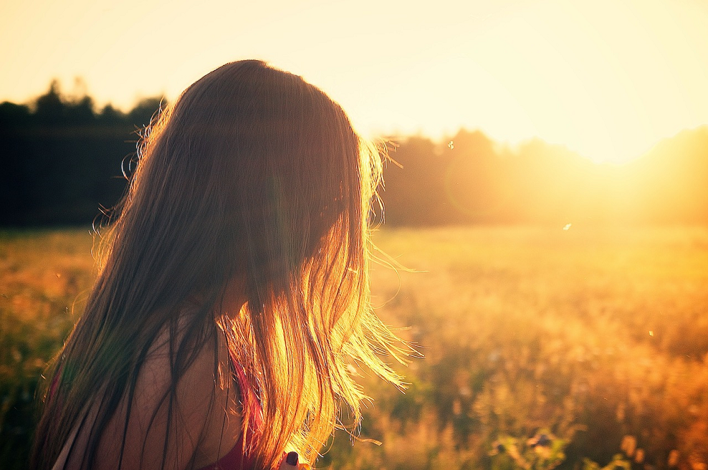 Woman stood in field during sunset thinking and being alone