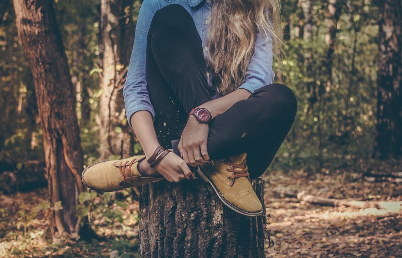 Girl sitting on a log in nature spending time on alone for her wellbeing