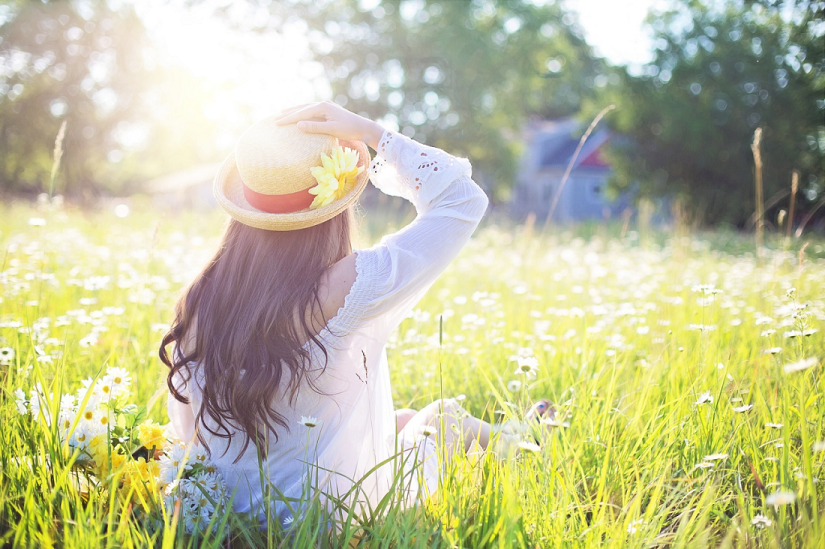 Girl sat in field with hat on and sun out, thinking about how she is good enough